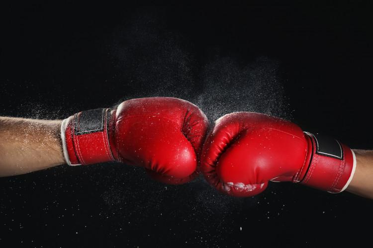 Men in boxing gloves on black background